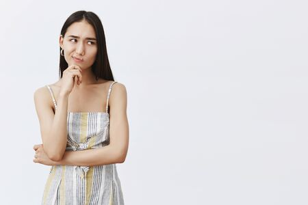 Hmm, let me think. Portrait of doubtful good-looking asian female in matching trendy outfit, smirking and gazing right while holding hand on chin, thinking, hesitating over gray background