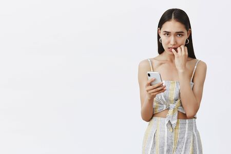 What should I do, help. Portrait of worried charming tanned girl with dark hair, biting fingernails and gazing with guilty and worried expression at camera, holding smartphone, making huge mistake