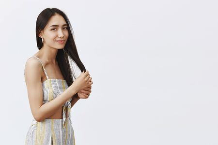 Beauty, hairstyle and haircare concept. Portrait of tender attractive young woman with clean skin, touching hair strands and gazing at camera with gentle smile, standing over gray background