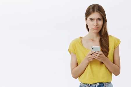 Waist-up shot of displeased gloomy charming european woman in yellow t-shirt frowning pursing lips in doubt and sadness holding smartphone feeling regret and dissatisfaction over grey wall 免版税图像