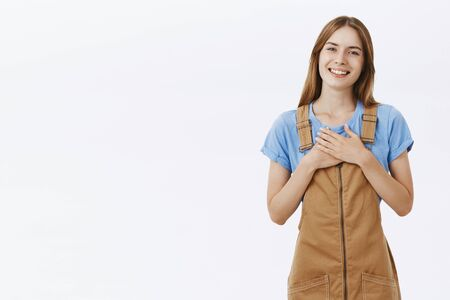 Indoor shot of charming grateful happy girl in brown dungarees over blue t-shirt holding palms on heart and smiling thankful posing over gray background delighted against gray background Stock Photo