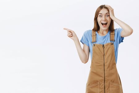 Portrait of amazed impressed good-looking caucasian female in brown overalls holding hand on head and pointing left feeling thrilled and surprised seing awesome person alive over gray wall Foto de archivo