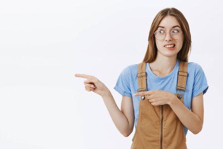 Chica de pie con chico espeluznante mostrando bicho raro a un amigo. Intensa mujer europea encantadora disgustada en peto marrón y gafas apretando los dientes y sonriendo de antipatía mirando y apuntando a la izquierda