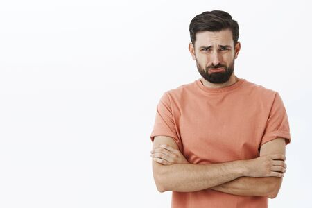 I thought you loved me. Crying bearded 30s guy frowning grimacing in sorrow holding hands crossed over body in defensive pose, whining, offended and upset with break-up, complaining on hard life