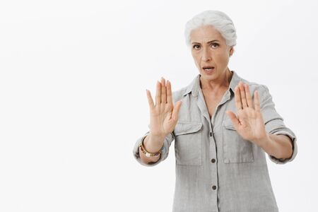 Serious-looking intense and wise elderly mother warn son to calm down raising palms, trying carefully talk to reduce pressure, asking relax and not worry, rejecting something or showing stop gesture