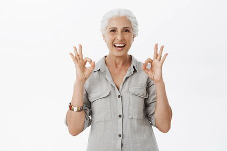 I recommend this place. Portrait of delighted and satisfied cute granny with grey hair in casual shirt showing okay or excellent gesture and smiling broadly approving great idea over gray background