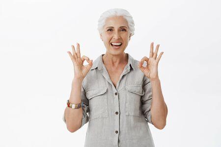 Recomiendo este lugar. Retrato de abuelita linda encantada y satisfecha con el pelo gris en camisa casual que muestra un gesto bien o excelente y una amplia sonrisa de aprobación de la gran idea sobre fondo gris