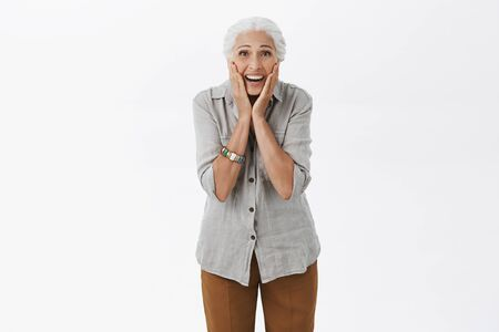 Senior woman surprised and happy like child receiving gift from children. Portrait of delighted and amused old woman with white hair touching cheeks with palms gazing amazed at camera over grey wall