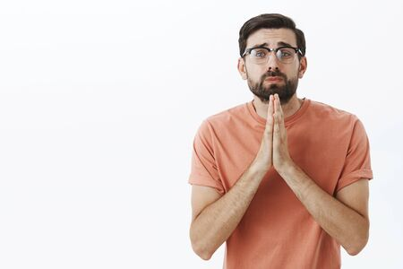 Please I need you help. Silly begging insecure nerdy guy in glasses stooping holding hands in pray gazing with cute sad expression at camera asking favor or lending money posing against gray wall
