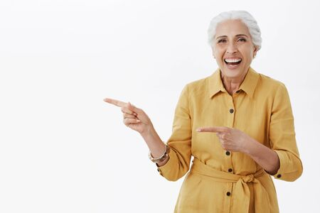 Portrait of delighted healthy and active pretty senior female in yellow trendy coat and bracelet laughing out loud from amusement standing entertained and charistmatic pointing left with forefingers