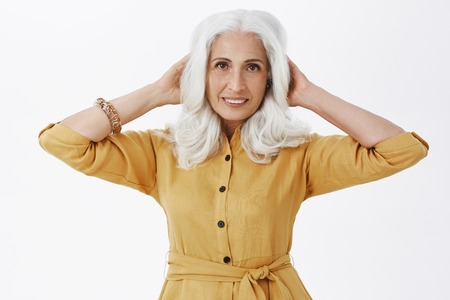 Portrait of stylish delighted and confident elderly woman touching hair and smiling self-assured at camera