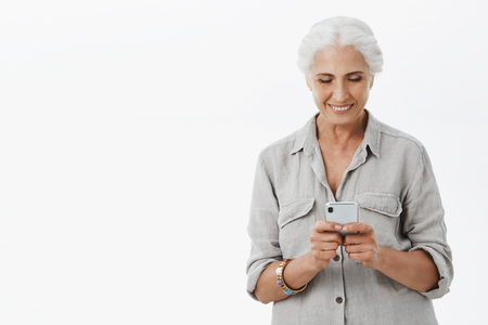 Portrait of charming pleased senior woman with grey hair holding telephone texting son smiling broadly staying in touch with gadget and internet