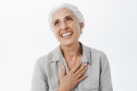 Happy and delighted grateful charming old lady with white hair holding palm on chest in thankful gesture.