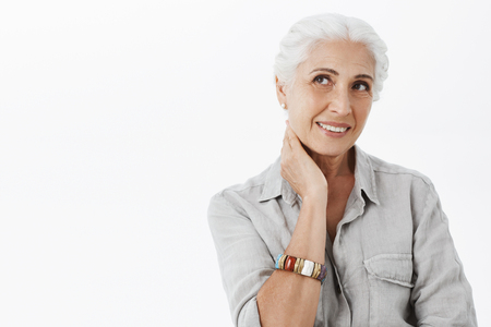 Waist-up shot of gentle delighted european senior female with white hair touching neck and smiling joyfully. Stock Photo