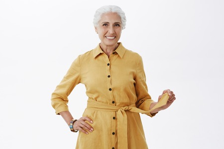 Portrait of energized and charismatic elderly woman in fashionable yellow coat.