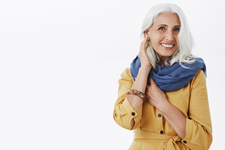 Charming fashionable and pleased grandmother with pretty grey hairstyle in trendy yellow coat and blue scarf touching hair gently and smiling at camera.