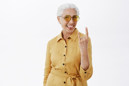 Portrait of joyful pleased and carefree enthusiastic grandmother with grey hair in stylish sunglasses and yellow coat sticking out tongue showing rock n roll gesture Stock Photo