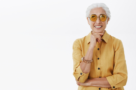 Waist-up shot of elegant good-looking and happy energized senior woman in trendy sunglasses and yellow trench coat. Stock Photo