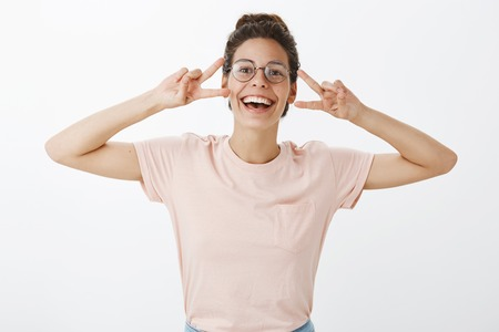 Mood boosts after eating tasty food let us have fun. Joyful charismatic and carefree young beautiful woman in round glasses smiling broadly having fun showing peace gestures near face over gray wall