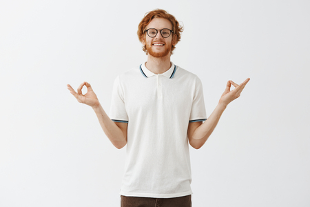 Happy calm good-looking redhead guy with beard in glasses and white casual shirt spreading hands aside in zen gesture meditating and smiling relieved Фото со стока