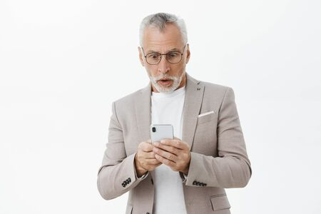 Waist-up shot of shocked mature male digital nomad in suit and glasses with grey hair and beard holding smartphone reacting surprised and impressed reading impressive message in cellphone screen