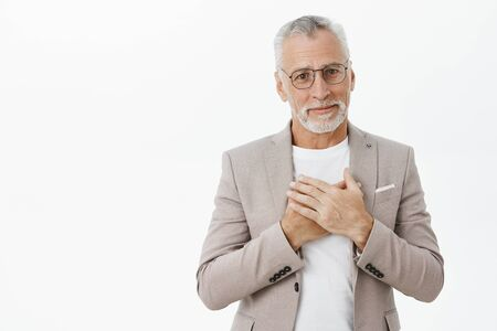 Kind and tender touched cute senior grandfather with white hair and beard in suit and glasses pressing palms to heart smiling sincere being grateful and thankful for gift and nice words Фото со стока