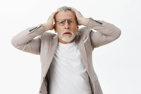 Portrait of concerned and troubled shocked senior man with white hair and beard in suit and glasses holding hands on head anxiously feeling worried learning bad news posing over gray background
