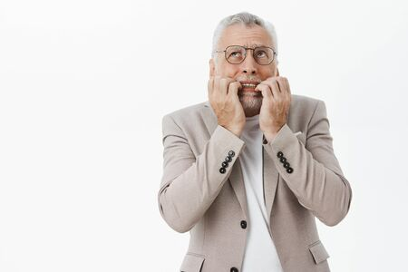 Portrait of concerned panicking and worried senior bearded man in glasses and suit biting fingers from nervousness and overreacting looking up scared standing intense over white background