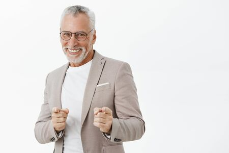 Het gotcha. Portrait of amused and happy carefree old man feeling energized ready to make money pointing at camera with finger gun gestures and smiling positive being in good mood over gray wall