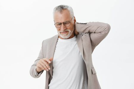 Man feeling pain in spine after hardworking sitting for long time. Portrait of displeased bothered mature male with white beard and hair in glasses touching back of neck complaining on pain Фото со стока