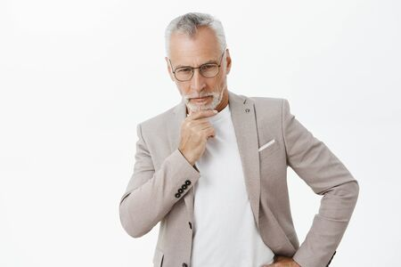 Portrait of intelligent wealthy and thoughtful attractive mature businessman with grey hair rubbing beard looking down with focused and determined expression thinking concentrating on work