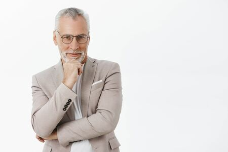 Intrigued and pleased good-looking old male with white beard and moustache in black frames and elegant suit holding hand on chin in thoughtful pose smiling pleased liking what hears over grey wall