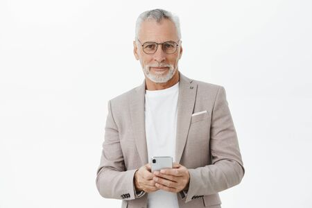 Portrait of stylish and smart confident senior businessman in glasses and elegant formal suit holding smartphone against chest smirking at camera pleased with new useful features of gadget Фото со стока