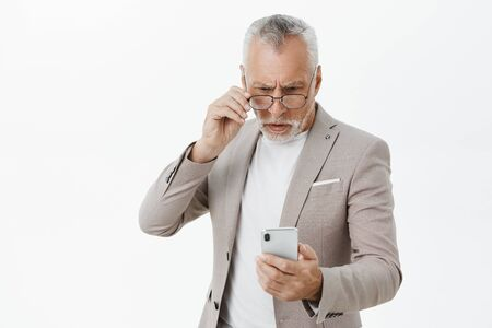 Portrait of confused old man trying understand how use new smartphone holding cellphone putting on glasses to look focused and determined standing questioned over gray background in suit Фото со стока