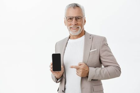 Delighted friendly handsome male with white beard and moustache in elegant suit and black frames holding cellphone pointing at smartphone screen showing image in gadget, smiling happily