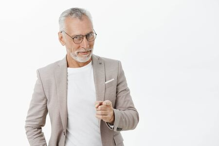 We need you man. Portrait of happy amused and tricky mature macho businessman in glasses and suit smiling looking and pointing at camera as if hinting or picking someone to join team