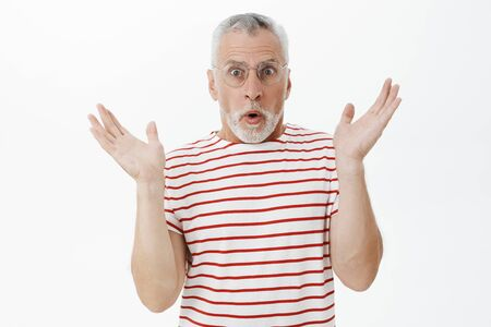 Waist-up shot of surprised handsome senior man with grey beard in prescribed glasses and striped t-shirt raising palms in amazement reacting on unxpected news opening mouth popping eyes at camera Zdjęcie Seryjne