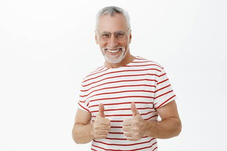 Happy optimistic and energized charismatic old man with beard in glasses and striped t-shirt showing thumbs up gesture and smiling broadly giving positive feedback against gray background