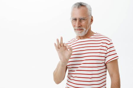 Old charismatic and self-assured man staying chill and cool showing okay gesture and smiling satisfied at camera assuring he got everything under control posing confident and assertive over grey wall Stock Photo