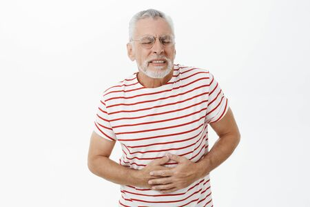 Portrait of intense bothered old man with grey beard and hair in glasses feeling pain and discomfort pressing hands to belly suffering from stomach ache having problems with health and eating disorder