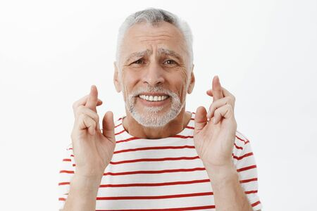 Intense worried senior retired grandfather with grey beard crossing fingers for good luck frowning clenching teeth praying making wish for wife getting cured standing nervous over gray wall Stock Photo