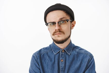 Doubtful and uncertain serious-looking bossy male entrepreneur in black beanie shirt and glasses raising one eyebrow in hesitation and disbelief standing unemotive and suspicious over gray background