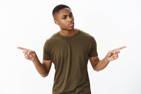 Studio shot of troubled serious-looking confused handsome african american male model looking right stuggling with choice, pointing sideways interested in buying new object but having doubts Stock Photo