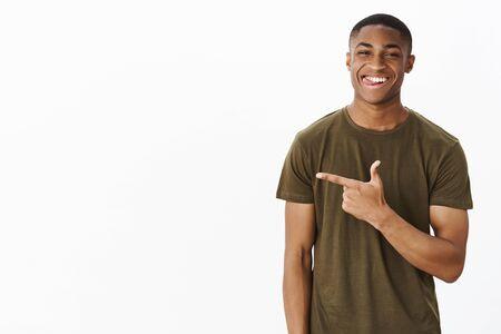 Tiro de cintura para arriba del carismático, coqueto y guapo deportista afroamericano sacando la lengua mientras sonríe travieso apuntando a la izquierda con una idea interesante y tortuosa, sonriendo de autosatisfacción Foto de archivo