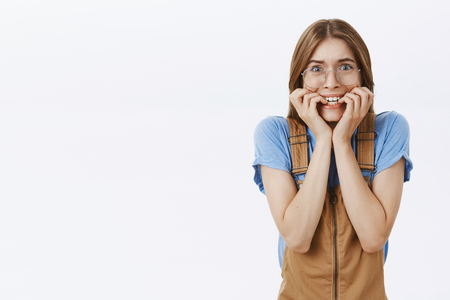 Waist-up shot of shocked and scared trembling female in brown overalls and glasses biting fingernails clenching teeth looking frightened and horrified posing over gray background 版權商用圖片