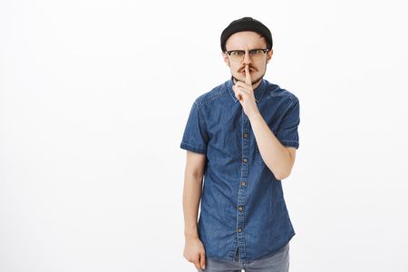 Irritated pissed angry guy with beard in beanie and glasses frowning shushing at camera with dissatisfied mad look asking keep quiet and not interrupt rehearsal of band over gray background Stock Photo