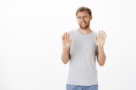 Guy trying refuse proposal being not in mood raising palms in rejection gesture clenching teeth and making sorry expression unwilling to go anywhere declining offer over white background Stock Photo
