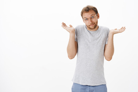 Silly and cute  adult bearded man in glasses and casual grey t-shirt shrugging with hands up smiling with sorry look being unaware and clueless over white 스톡 콘텐츠