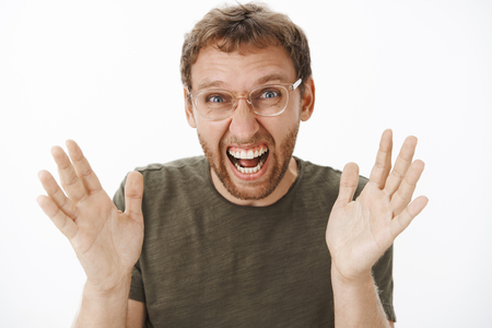 Close-up shot of excited overwhelmed funny european man with bristle in glasses raising palms and yelling from joy and happiness being amazed and joyful with awesome news posing in dark-green t-shirt