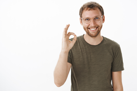 Portrait of friendly good-looking helpful european guy in glasses with beard showing ok or okay gesture and smiling assuring customer deal gonna be signed Stok Fotoğraf - 115100644